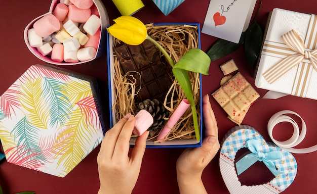 Top view of female hand putting marshmallow into a present box with yellow color tulip flower , dark chocolate bar , cone and straw on dark red table with a box filled with marshmallow
