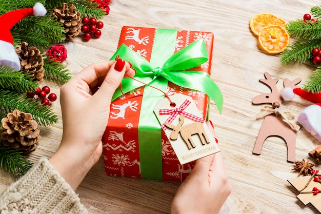Top view of female hand tie up new year present on festive wooden background