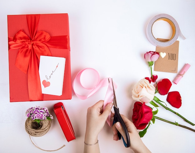 La vista superiore della mano femminile con le forbici taglia un nastro rosa e le rose rosse e bianche di colore con un contenitore di regalo rosso con un arco su fondo bianco
