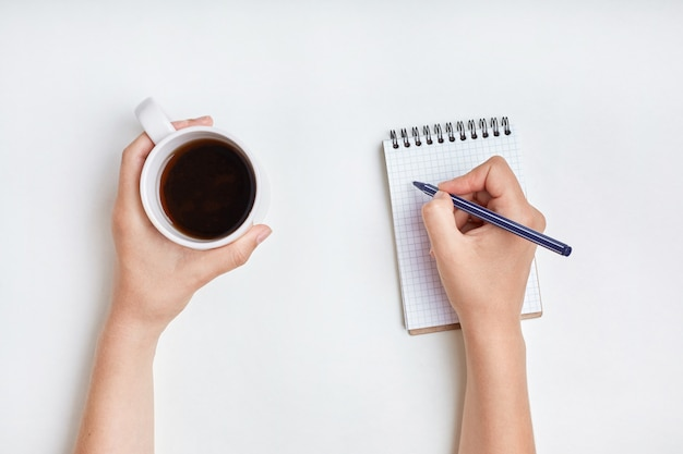 Top view of female hand writes in spiral notebook, takes notes with cup of tea. woman writes in her diary