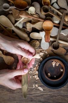 上面図女性の手はストックナイフで木のスプーンを彫る
