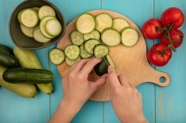 Vista dall'alto delle mani femminili tritare un cetriolo fresco su una tavola di cucina in legno con coltello con pomodori, cetrioli e zucchine isolato su una parete di legno blu