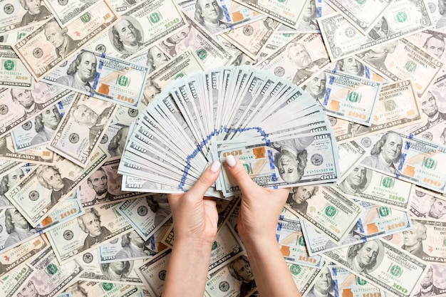 Top view of female hands counting money on different dollar . debt . investment
