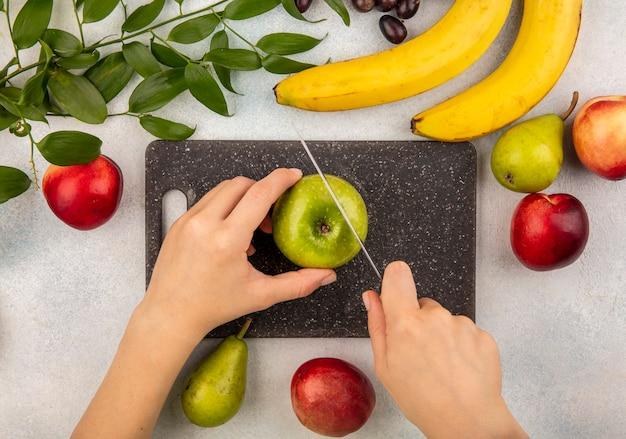 Top view of female hands cutting apple with knife on cutting board and grape pear banana peach with leaves on white background