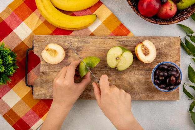 Top view of female hands cutting apple with knife and half cut peach and grape berries on cutting board and banana on plaid cloth with peaches and leaves on white background