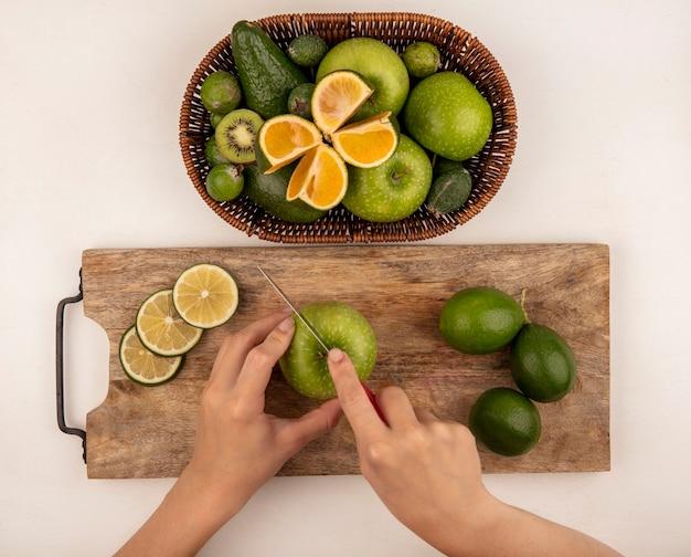 Vista dall'alto delle mani femminili che tagliano una mela su una tavola da cucina in legno con un coltello con un secchio di mele verdi kiwi feijoas e limette su un muro bianco