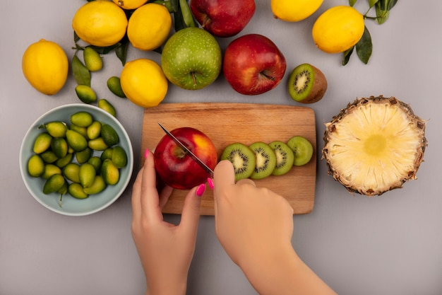 Top view of female hands cutting apple on a wooden kitchen board with knife with kinkans on a bowl with apples kiwi pineapple and lemons isolated on a white wall