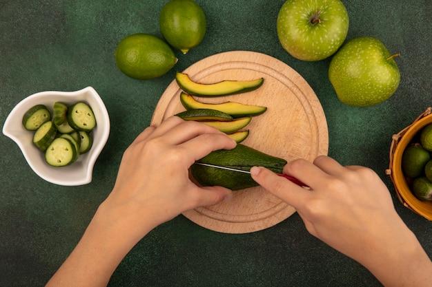 Vista dall'alto delle mani femminili che tagliano l'avocado con il coltello su una tavola di cucina in legno con fette di cetriolo tritato su una ciotola con limette e mele verdi isolate su una superficie verde