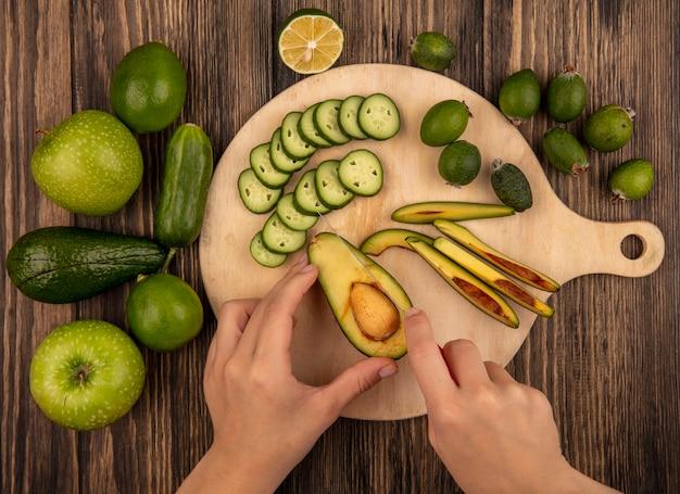 Vista dall'alto delle mani femminili che tagliano un avocado con il coltello su una tavola di cucina in legno con fette di cetriolo tritato con cetriolo intero limette mele verdi e avocado isolato su una superficie di legno