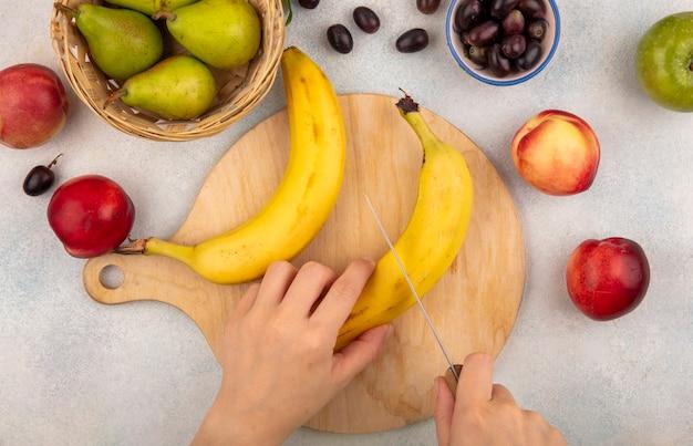 Vista superiore delle mani femminili che tagliano la banana con il coltello sul tagliere e la mela della pesca della pera dell'uva su fondo bianco