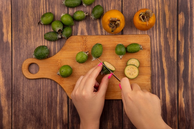 Vista dall'alto delle mani femminili che tagliano feijoa su una tavola da cucina in legno con coltello con frutti di cachi freschi e feijoas isolati su una parete in legno