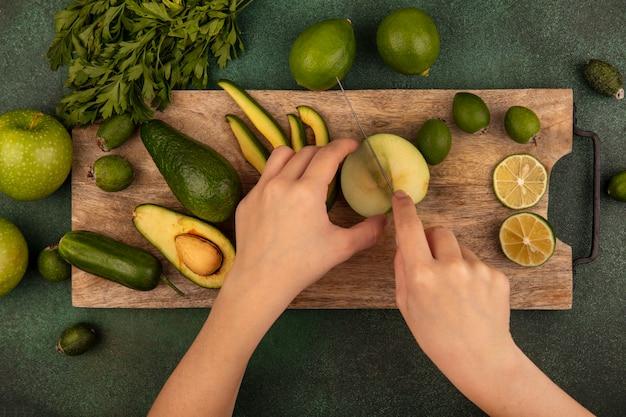 Vista dall'alto delle mani femminili che tagliano la mela fresca con il coltello su un tagliere di cucina in legno con limes feijoas avocado mele verdi e prezzemolo isolato su una parete verde