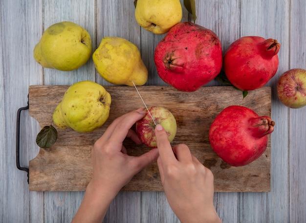 Vista superiore delle mani femminili che tagliano la mela fresca su una tavola di cucina in legno con il coltello su un fondo di legno grigio