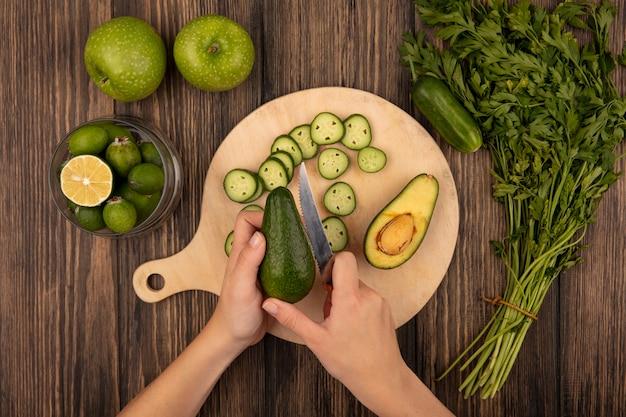Vista dall'alto delle mani femminili che tagliano un avocado fresco con il coltello su una tavola da cucina in legno con feijoas su una ciotola di vetro con mele verdi e prezzemolo isolato su uno sfondo di legno