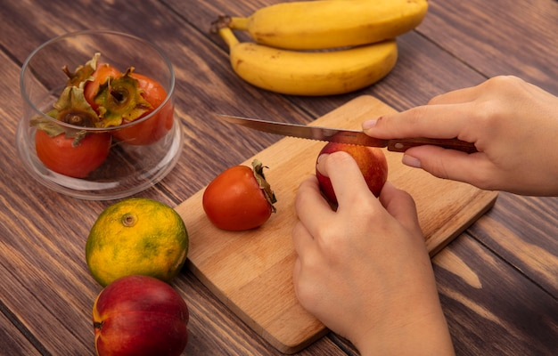 Top view of female hands cutting a fresh peach on a wooden kitchen board with knife with tangerine and bananas isolated on a wooden wall