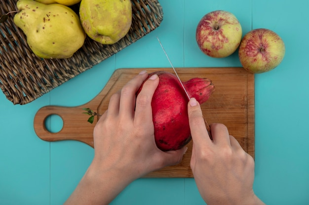 Top view of female hands cutting fresh pomegranate on a wooden kitchen board with knife on a blue background