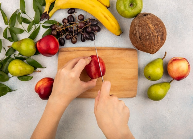 Top view of female hands cutting peach with knife on cutting board and grape pear coconut banana apple with leaves on white background