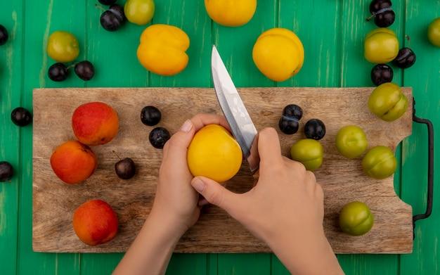 Vista dall'alto delle mani femminili che tagliano la pesca con il coltello su una tavola di cucina in legno con prugnole e pesche isolate su un fondo di legno verde