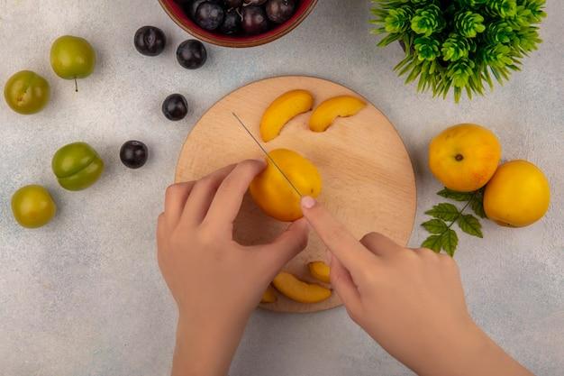 Vista dall'alto delle mani femminili che tagliano la pesca su un tagliere di cucina in legno con coltello con prugne ciliegia verde con prugnole viola scuro su sfondo bianco