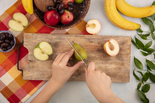 Top view of female hands cutting pear with knife and half apple and peach on cutting board and basket of peach grape coconut on plaid cloth with bananas and leaves on white background