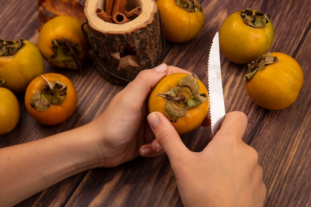 Top view of female hands cutting persimmon fruit on a wooden table