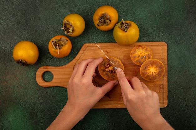 Vista dall'alto delle mani femminili che tagliano i frutti di cachi con il coltello su una tavola di cucina in legno su uno sfondo verde