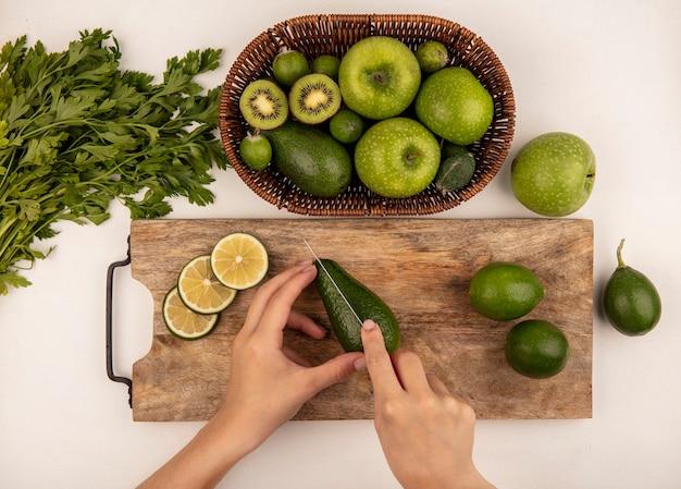 Vista dall'alto di mani femminili taglio avocado maturo con coltello su una tavola di cucina in legno con limette con mele su un secchio su sfondo bianco