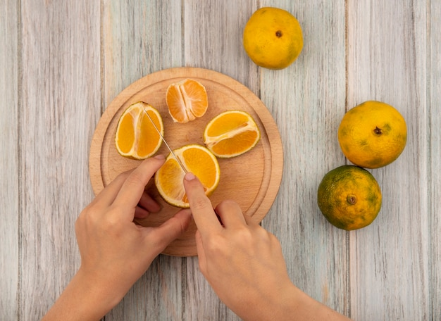 Top view of female hands cutting a tangerine on a wooden kitchen board with knife on a grey wooden surface