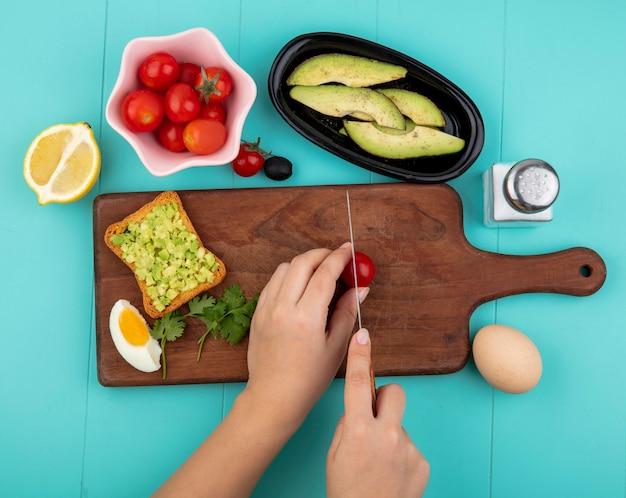 Vista dall'alto delle mani femminili che tagliano il pomodoro con un coltello sul bordo della cucina in legno con i pomodori sulla ciotola di fette di avocado e limone sul blu