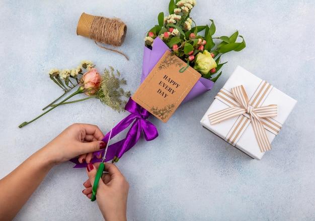 Vista dall'alto delle mani femminili che tagliano il nastro viola del mazzo di fiori con foglie su bianco
