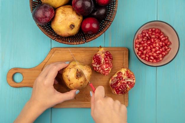 Vista dall'alto delle mani femminili che tagliano i melograni gialli su una tavola da cucina in legno con un coltello con i semi di melograno su una ciotola su una superficie blu