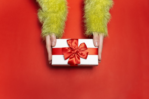Top view of female hands in green sweater, holding a white gift box with red ribbon on background of red color.