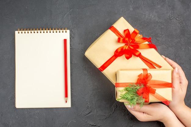 Vista dall'alto mani femminili che tengono regali di natale grandi e piccoli in carta marrone legati con una matita per quaderni con nastro rosso su sfondo scuro