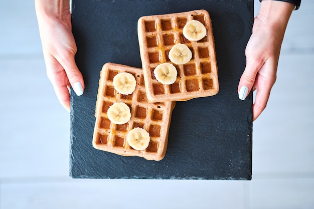 Top view of female hands holding black plate with belgian waffles
