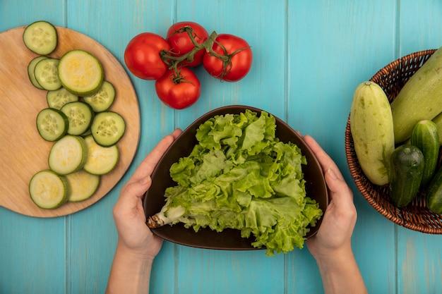 Vista dall'alto delle mani femminili che tengono una ciotola di lattuga fresca con un secchio di cetrioli e zucchine con pomodori isolati su una superficie di legno blu