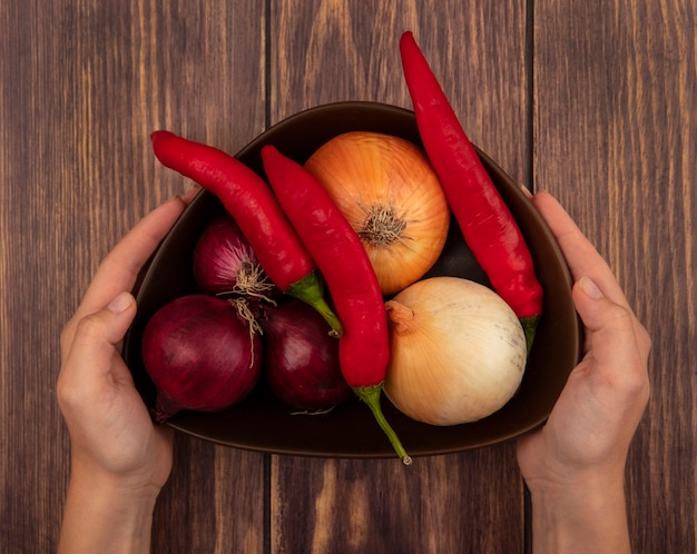 Vista dall'alto delle mani femminili che tengono una ciotola di verdure fresche come cipolle peperoni su una superficie di legno