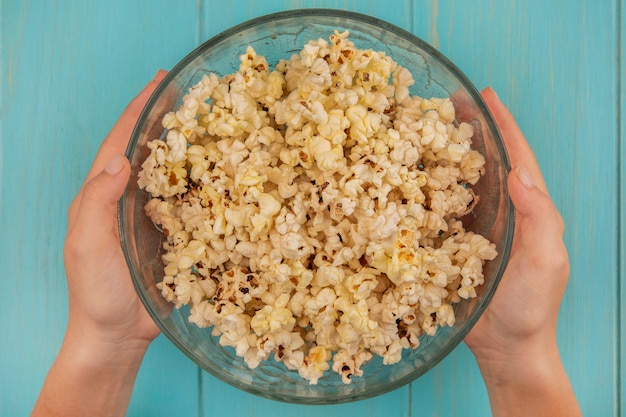 Top view of female hands holding a bowl of popcorns on a blue wooden table