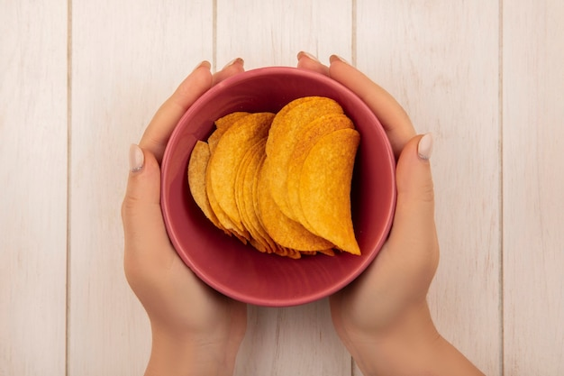 Top view of female hands holding a bowl of tasty crispy chips on a beige wooden table