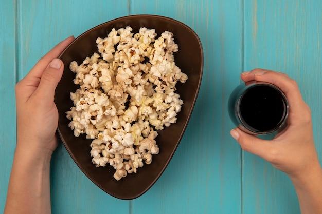 Vista dall'alto delle mani femminili che tengono una ciotola di gustosi popcorn in una mano e nell'altra un bicchiere di cola su un tavolo di legno blu