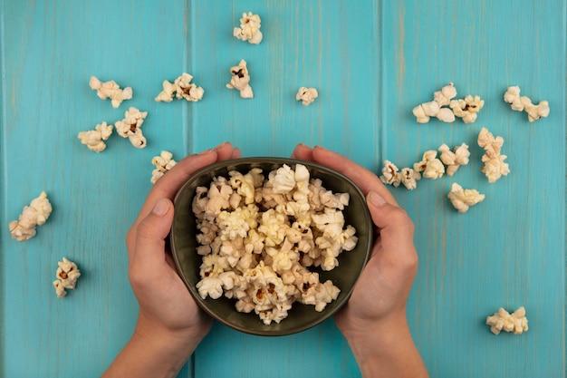 Vista dall'alto delle mani femminili che tengono una ciotola di gustosi popcorn con popcorn isolati su un tavolo di legno blu