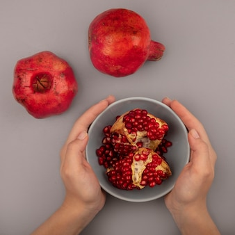 Top view of female hands holding a bowl with fresh pomegranates