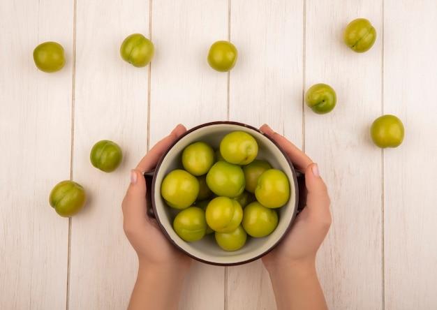 Vista dall'alto delle mani femminili che tengono una ciotola con prugna ciliegia verde su un fondo di legno bianco