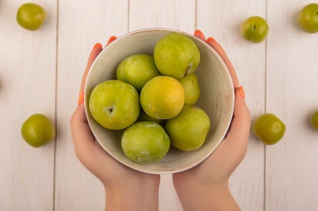 Vista dall'alto delle mani femminili che tengono una ciotola con prugne ciliegia verdi con prugne ciliegia verdi isolate su un fondo di legno