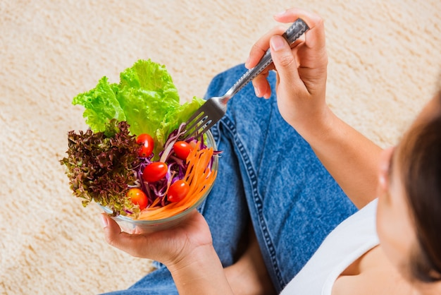 Top view of female hands holding bowl with green lettuce salad on legs