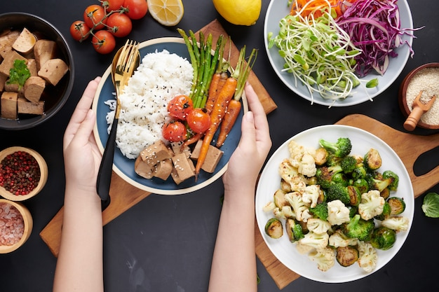 Top view of female hands holding bowl with mixed vegetables salad, young woman eating fresh salad meal vegetarian.