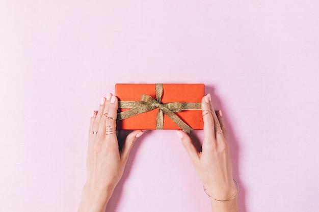 Top view of female hands holding a box with gift