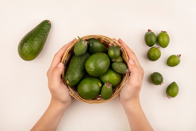 Vista dall'alto delle mani femminili che tengono un secchio di frutta fresca come lime di feijoas con feijoas e avocado isolato su una superficie bianca