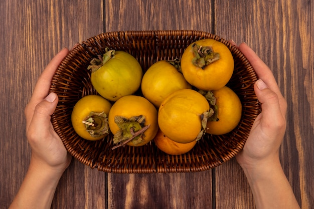 Top view of female hands holding a bucket of fresh orange persimmon fruits on a wooden table