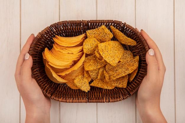 Vista dall'alto delle mani femminili che tengono un secchio con patatine croccanti su un tavolo di legno beige