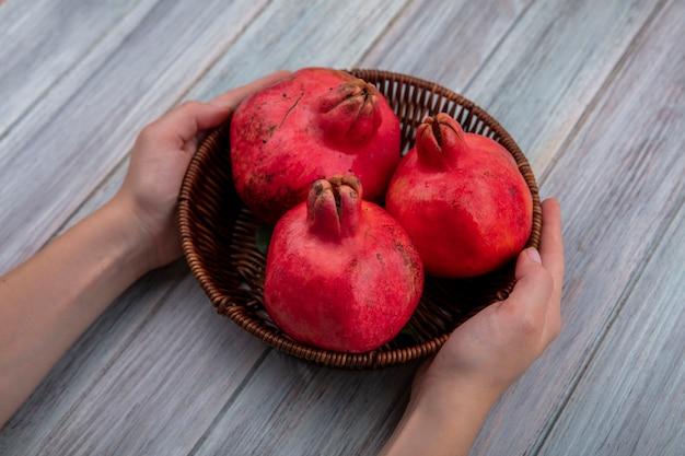 Vista dall'alto delle mani femminili che tengono un secchio con melograni freschi rossi su un fondo di legno grigio